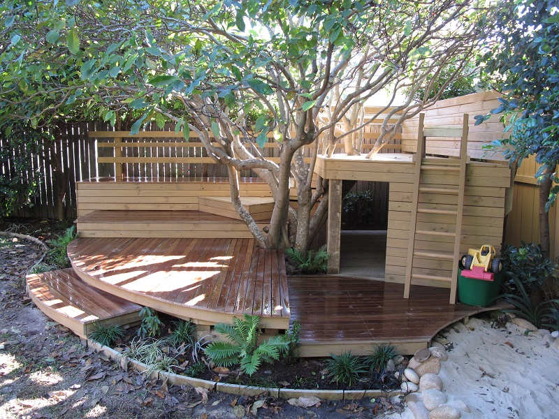 timber cubby and treehouse wrapped around magnolia tree kids house and play garden child friendly garden design and landscaping - Garden Design Kids